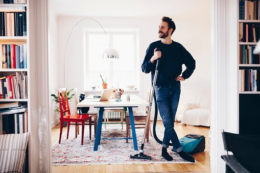 Photo of a man standing witha  vacuum cleaner in dining room at home  | Photo: Getty Images
