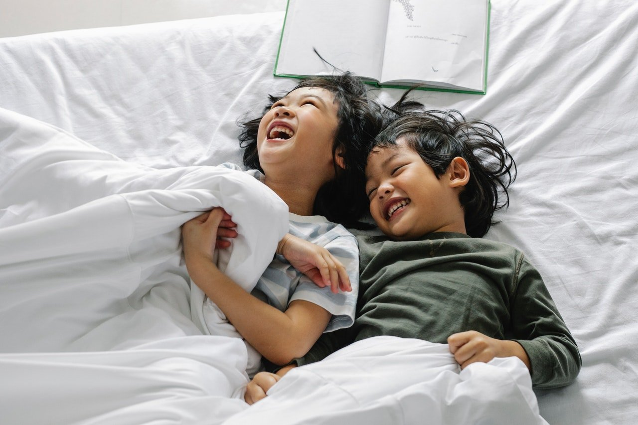 Two kids smiling while lying on the bed   Photo: Pexels