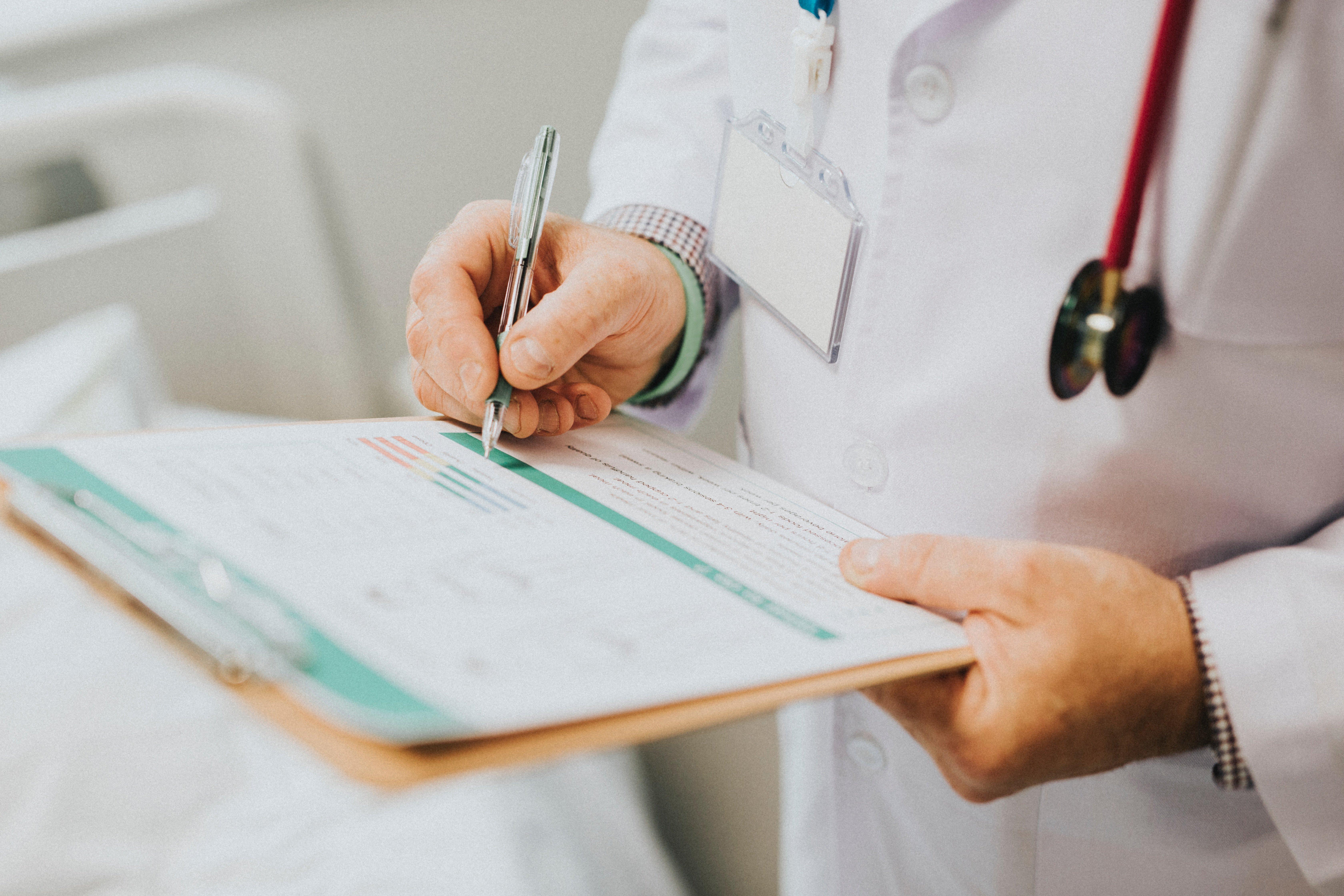 Un Docteur écrivant sur papier | Source : Unsplash