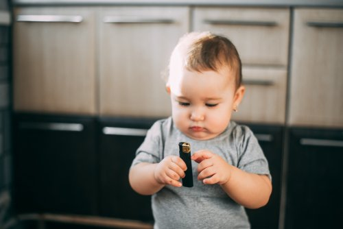 Baby tries to light black lighter.| Photo: Shutterstock.