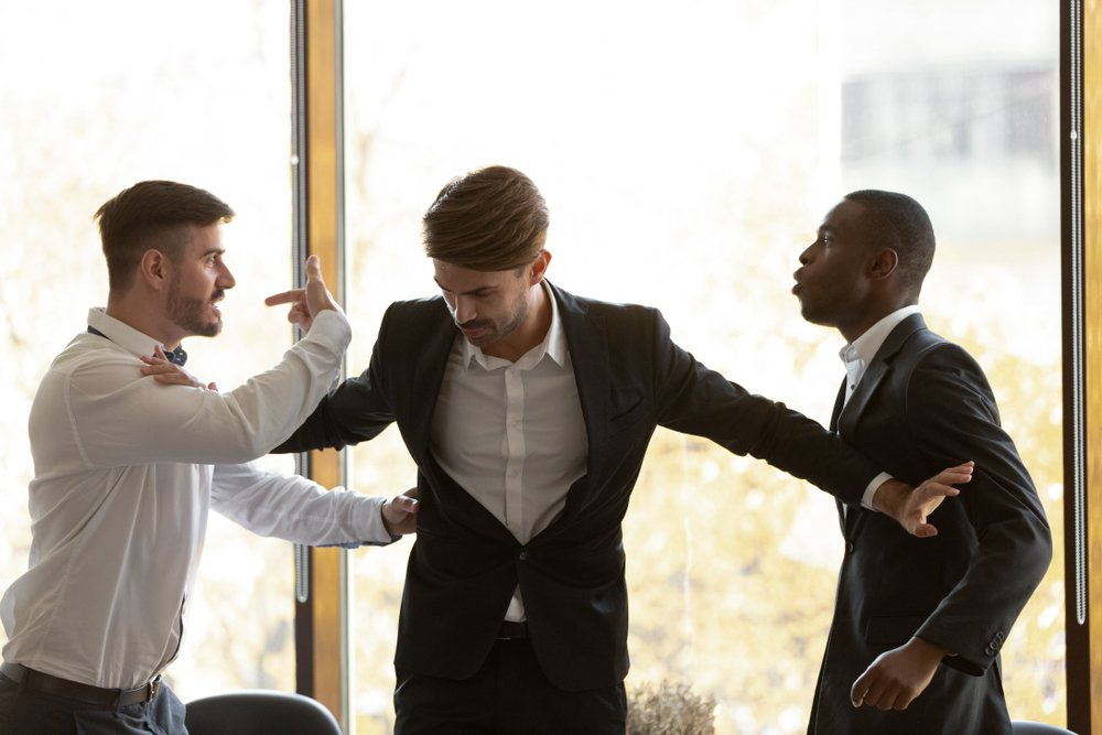 A photo of a man trying to stop two other men from fighting   Photo: Shutterstock