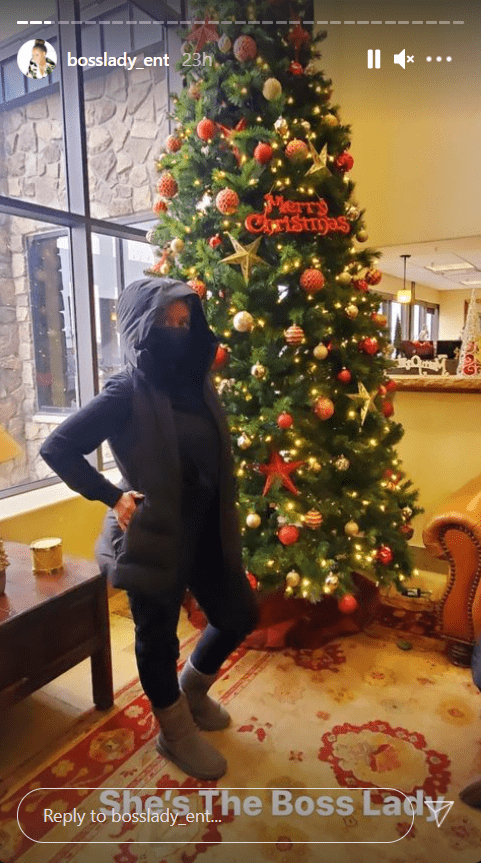 Shante Broadus, dressed in black, poses in front of a Christmas tree | Photo: Instagram/bosslady_ent