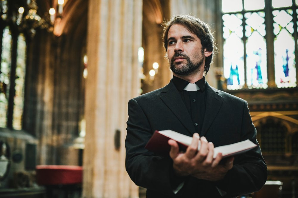 A Christian priest standing by the altar. | Photo: Shutterstock
