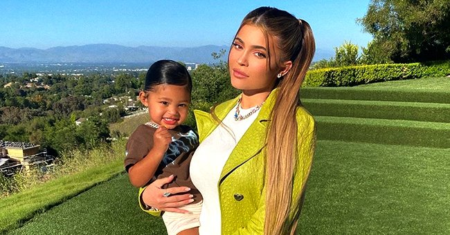 Kylie Jenner Stuns in Lime Green Coat While Holding Daughter Stormi on Scott Disick's Birthday