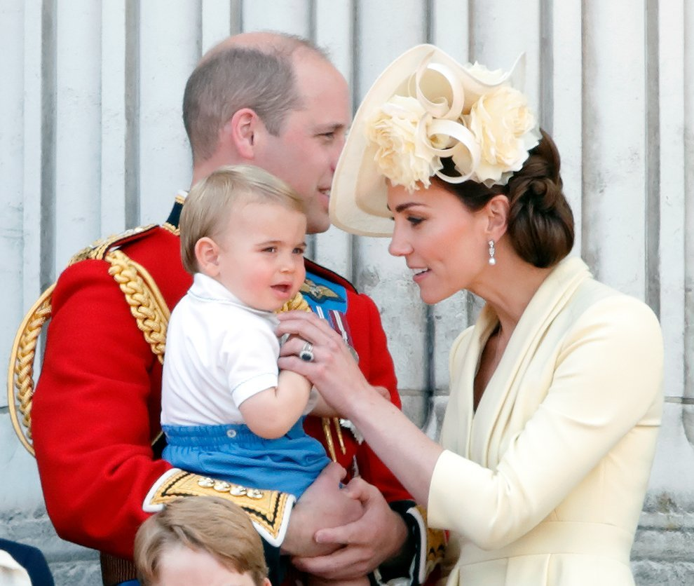 Kate Middleton removes Prince Louis' finger from his mouth as he sits in Prince William's arms at Trooping the Color | Photo: Getty Images