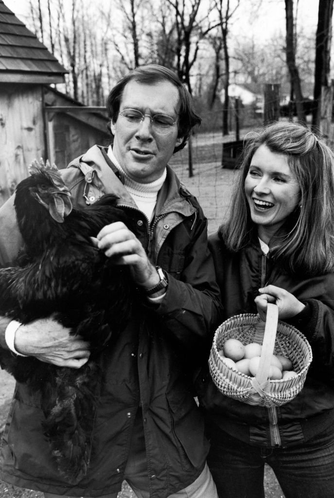 Publisher Andy Stewart holding a black Cochin hen and wife, caterer Martha, holding a basket of eggs in barnyard of their home | Getty Images