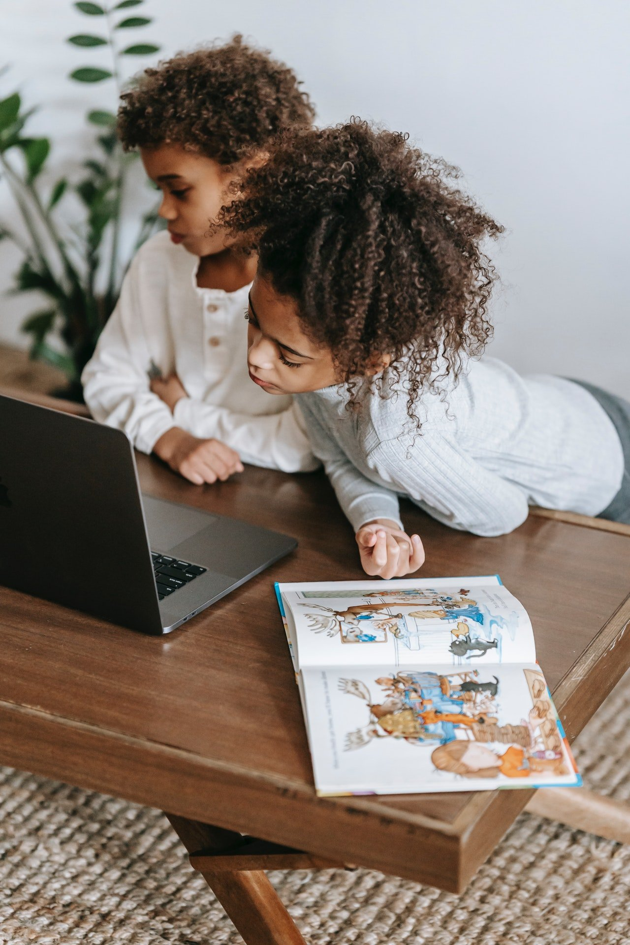 Two kids looking at a laptop   Source: Pexels