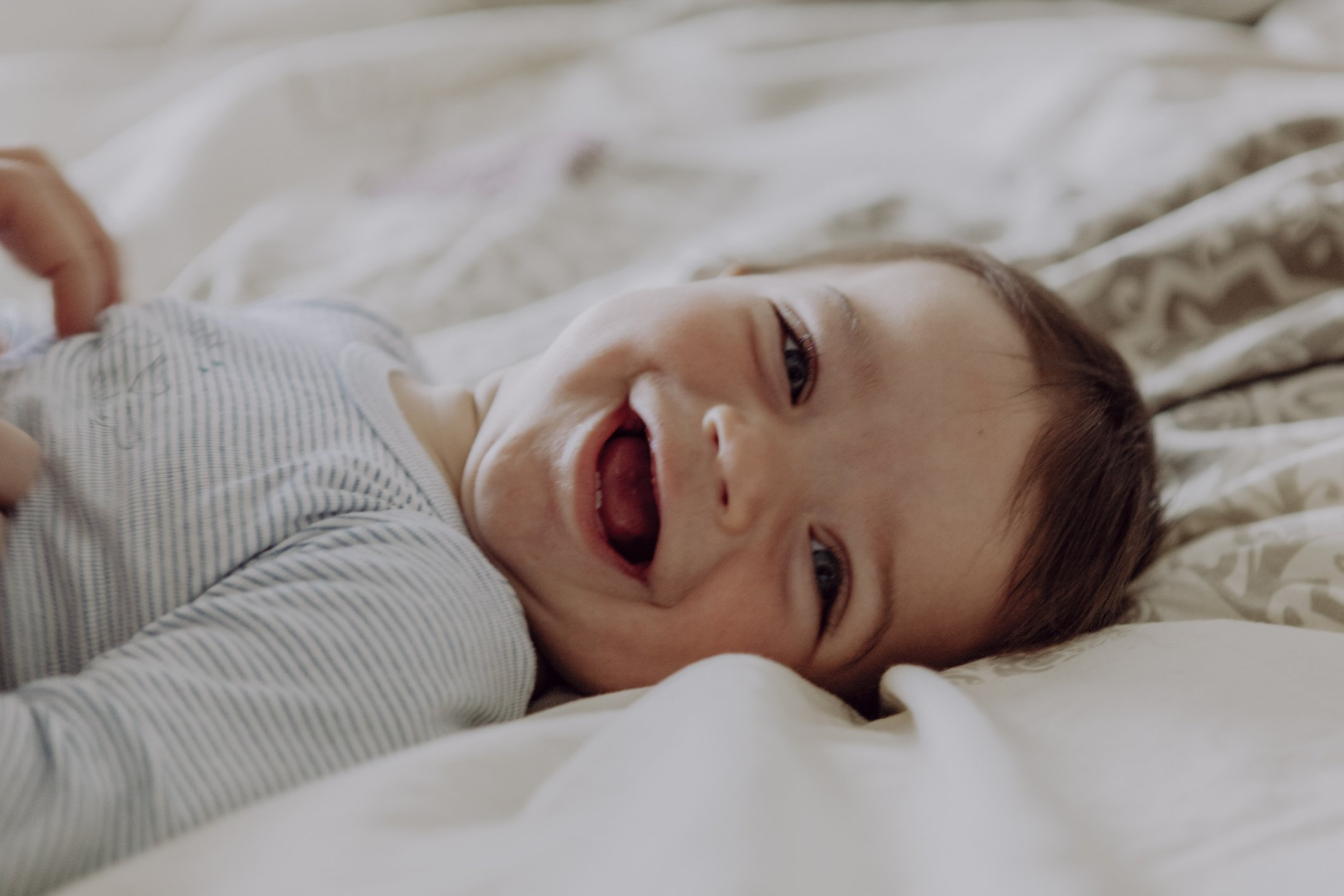 A portrait picture of a baby happily laughing lying on the bed. | Photo: Getty Images