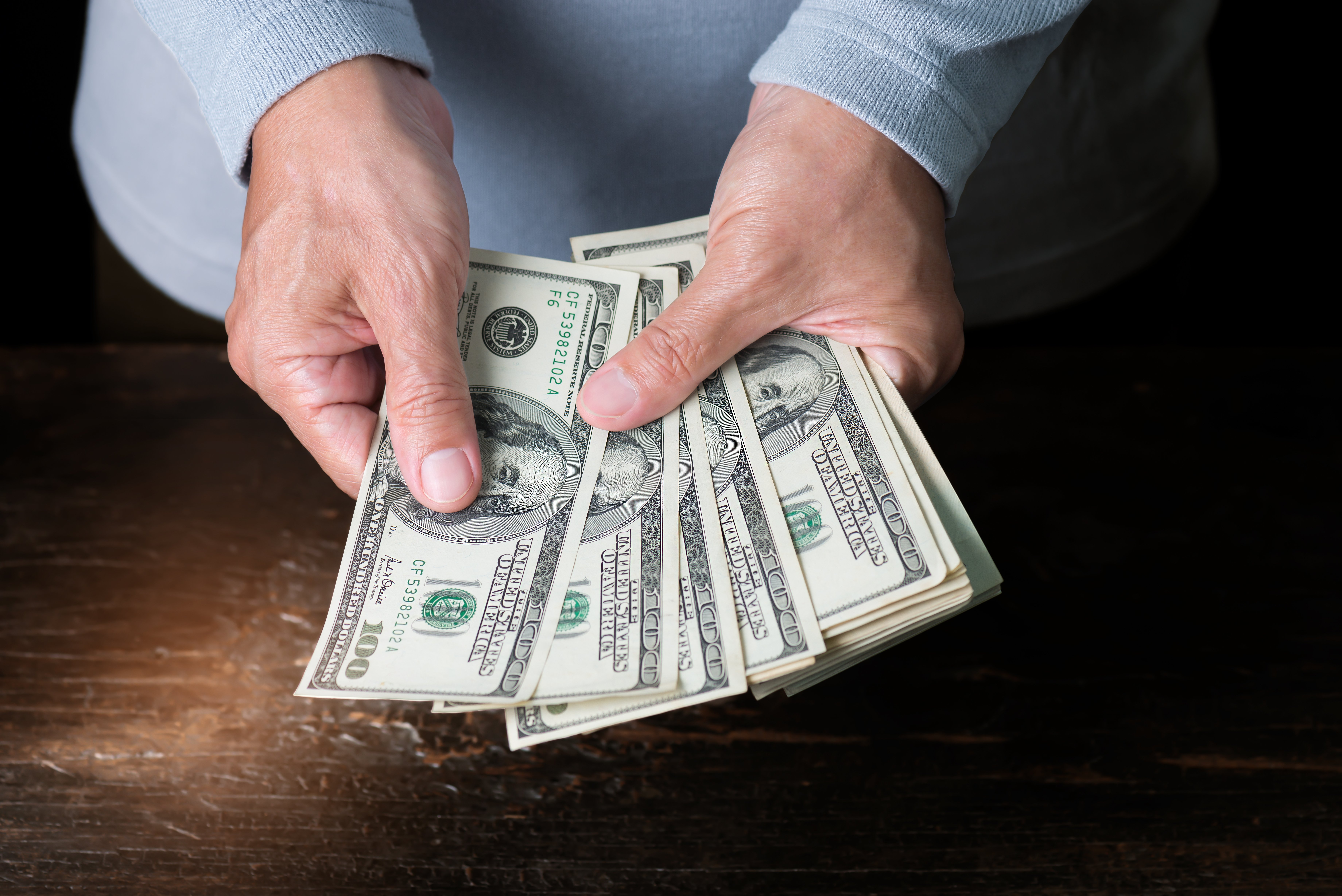 Un homme qui tient plusieurs billets d'argent | Photo : Shutterstock