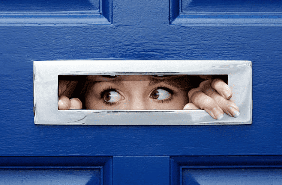 A young woman peeping through a letterbox on the front of a blue door | Source: Getty Images