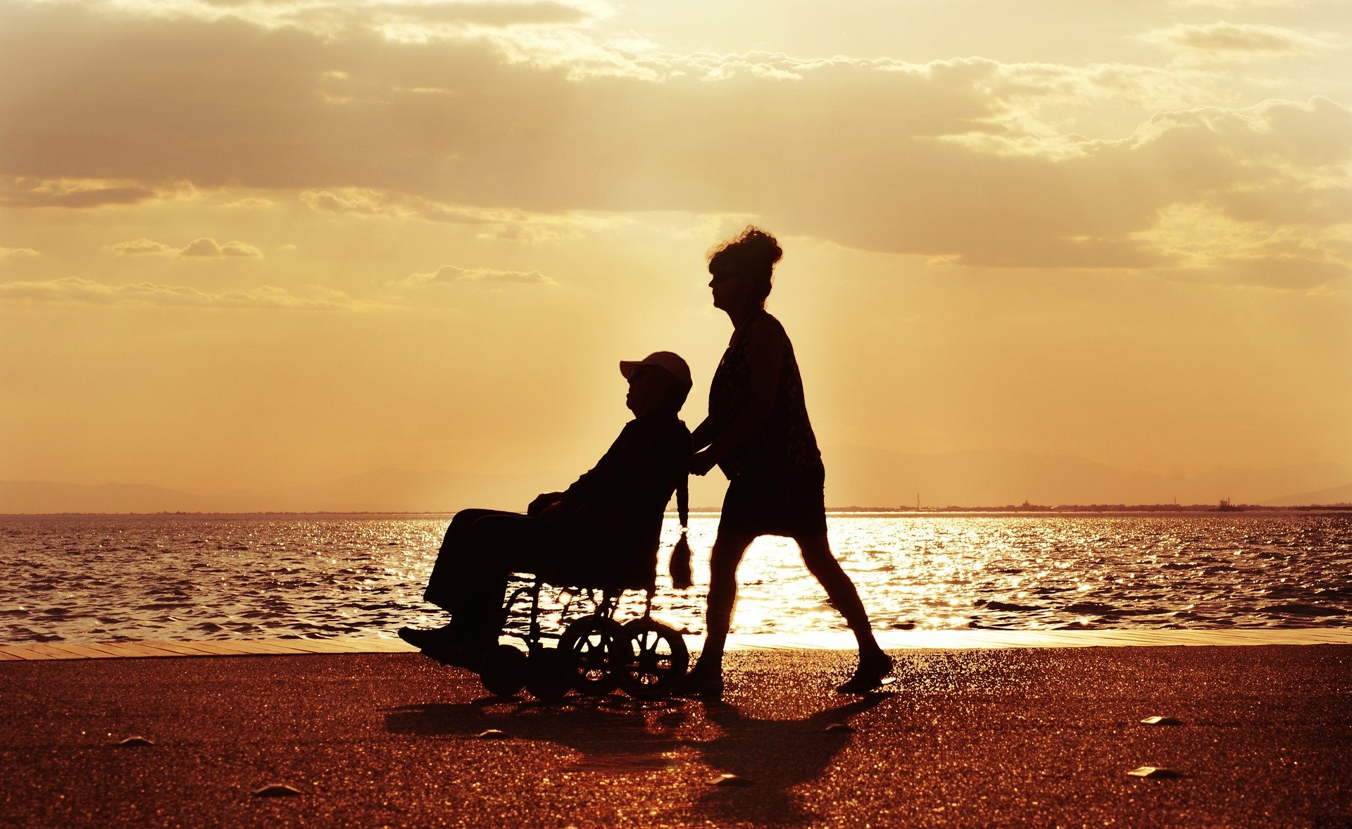 A woman pushing a wheelchair bound person along the beach. | Source: Pixabay.