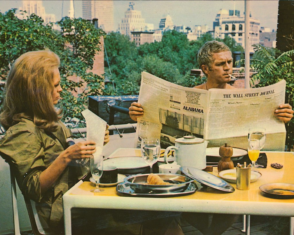 Faye Dunaway as Vicki Anderson and Steve McQueen (1930 - 1980) as Thomas Crown, reading the Wall Street Journal over breakfast in 'The Thomas Crown Affair', 1968.   Source: Getty Images