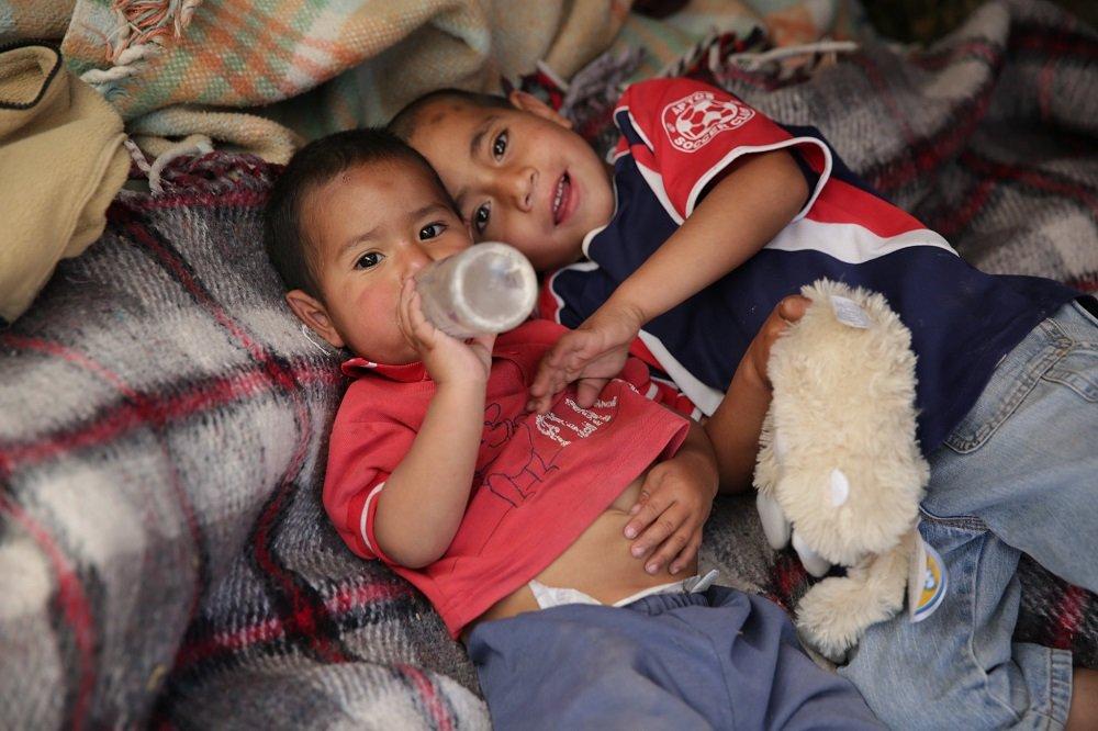 Niños sin hogar recostados sobre mantas. | Imagen: Flickr