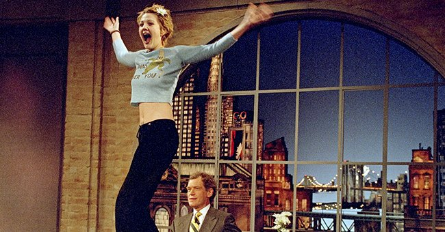 Drew Barrymore turns to the audience after flashing host David Letterman during a taping of the Late Show with David Letterman , April 1995 | Source: Getty Images