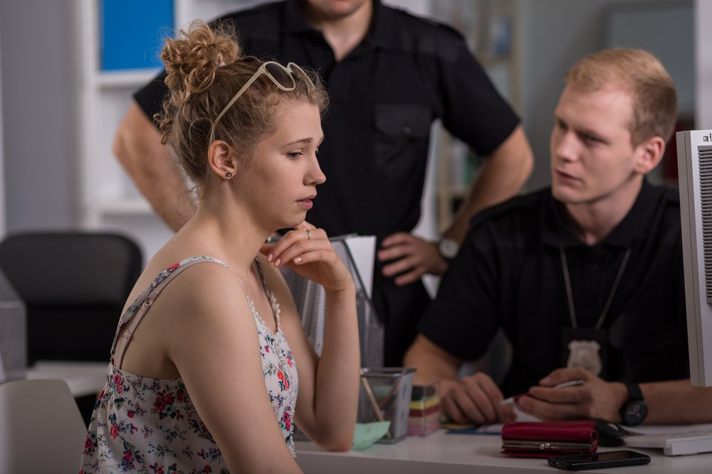 Shot of a young woman talking to two policemen at a police station | Photo: Shutterstock