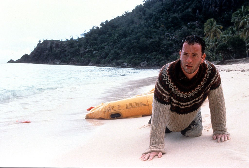 Tom Hanks washed up on the beach of an island in a scene from the film 'Cast Away', 2000.  | Source: Getty Images