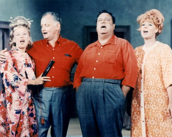 "Joyce Randolph, Art Carney, Jackie Gleason, and Audrey Meadows stand in a group singing in an image issued publicity for the television series, ""The Honeymooners,"" circa 1955. 