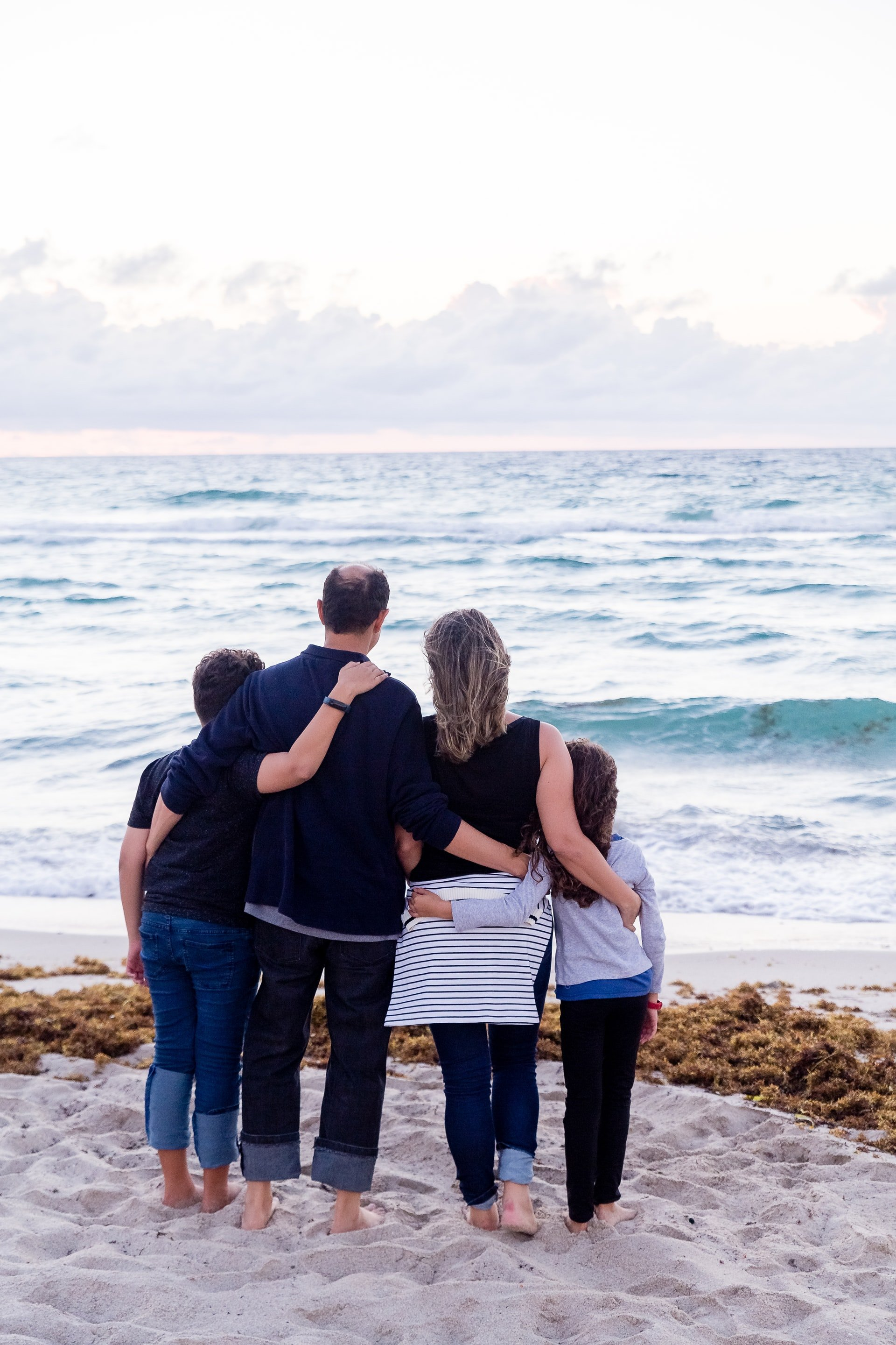 Couple standing with their children at the beach   Source: Unsplash