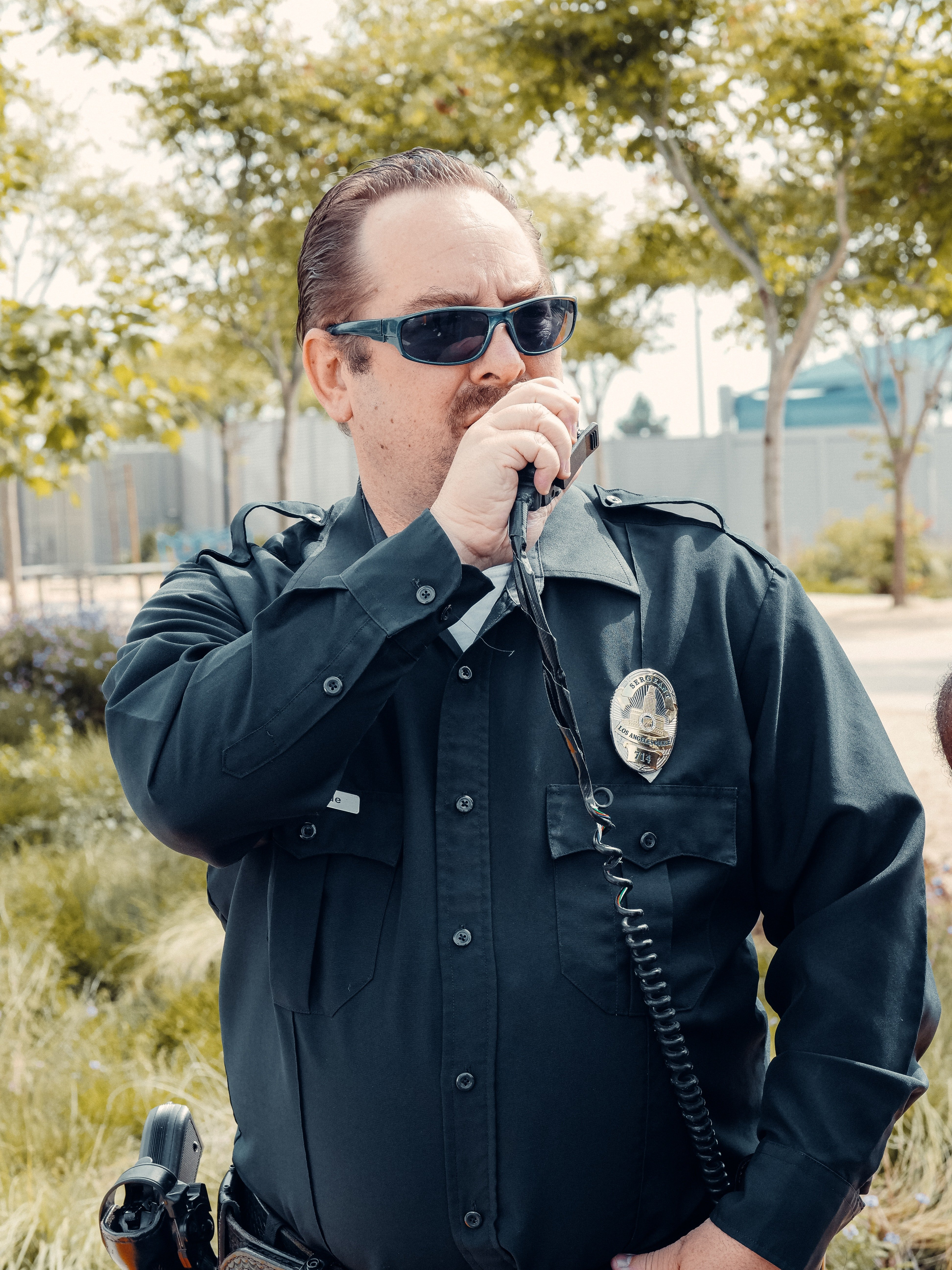 Pictured - A policeman in his uniform wearing sunglasses and speaking on the radio   Source: Pexels