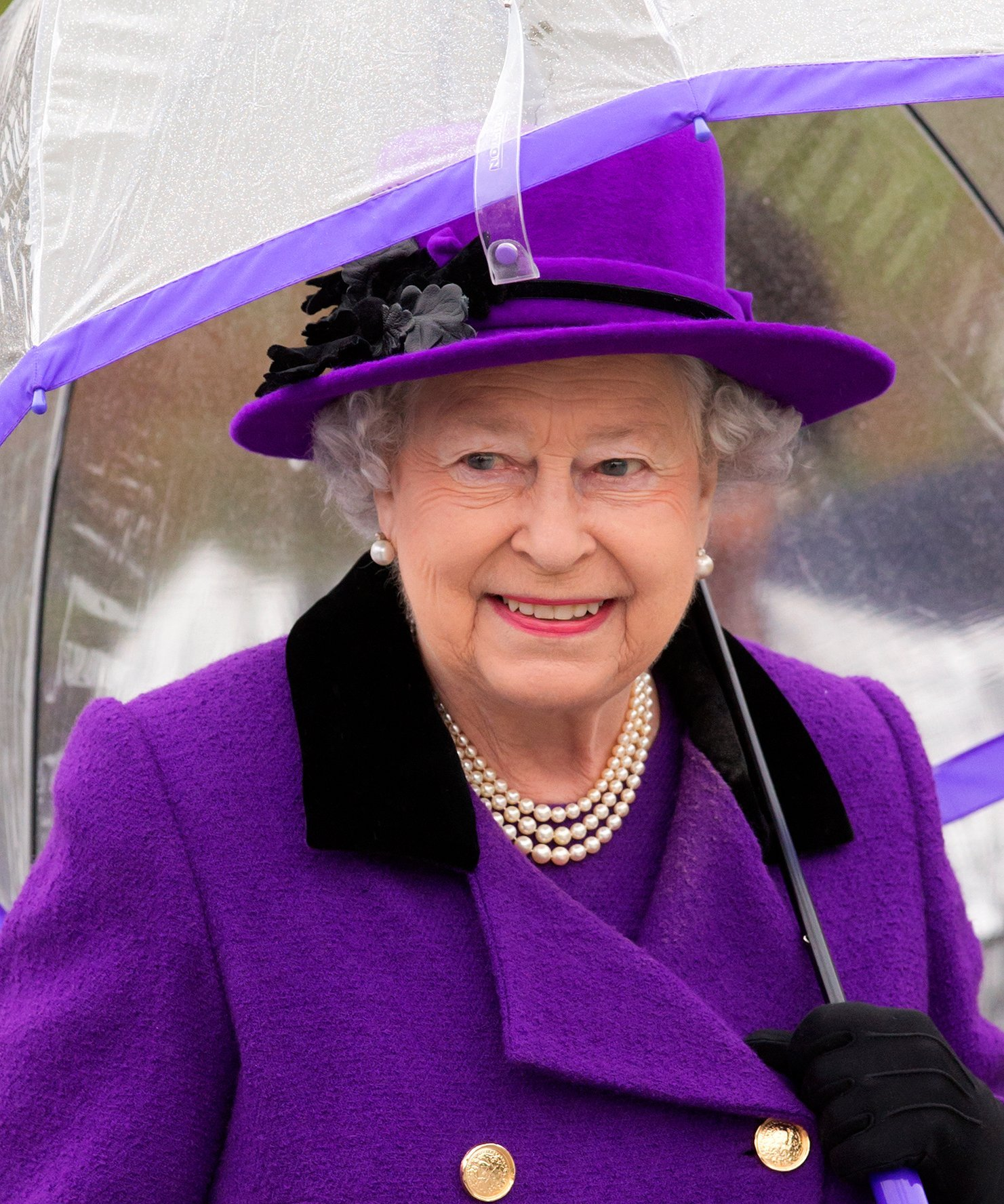 Queen Elizabeth II shelters under an umbrella as attends the opening of the newly developed Jubilee Gardens on October 25, 2012 | Photo: Getty Images