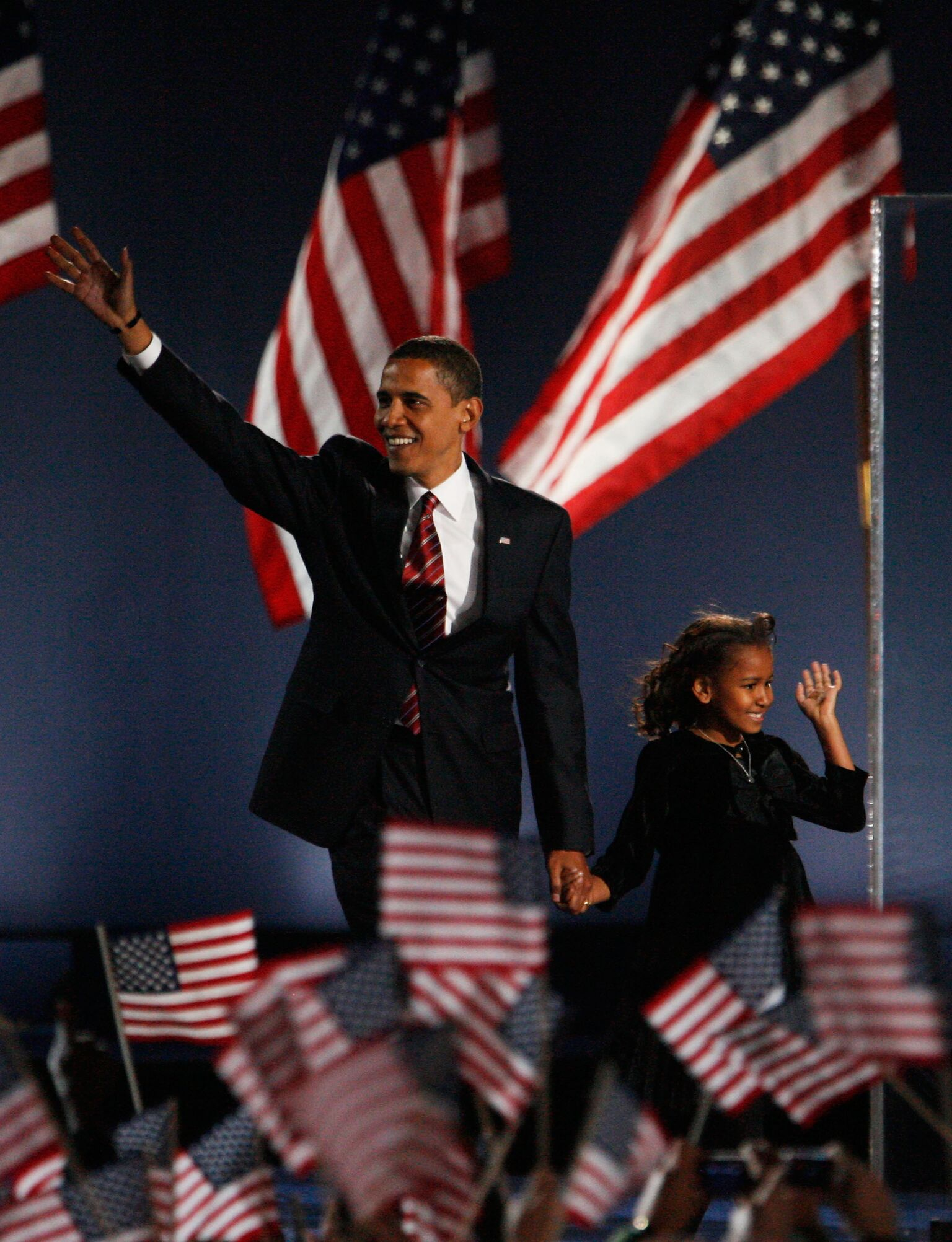 President elect Barack Obama and his daughter Sasha wave to Obama supporters during an election night gathering in Grant Park | Getty Images
