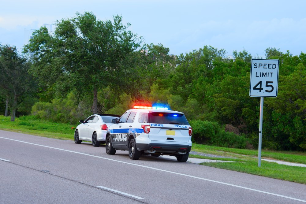 A police vehicle with flashing red and blue lights pulled over behind a car. | Photo: Shutterstock