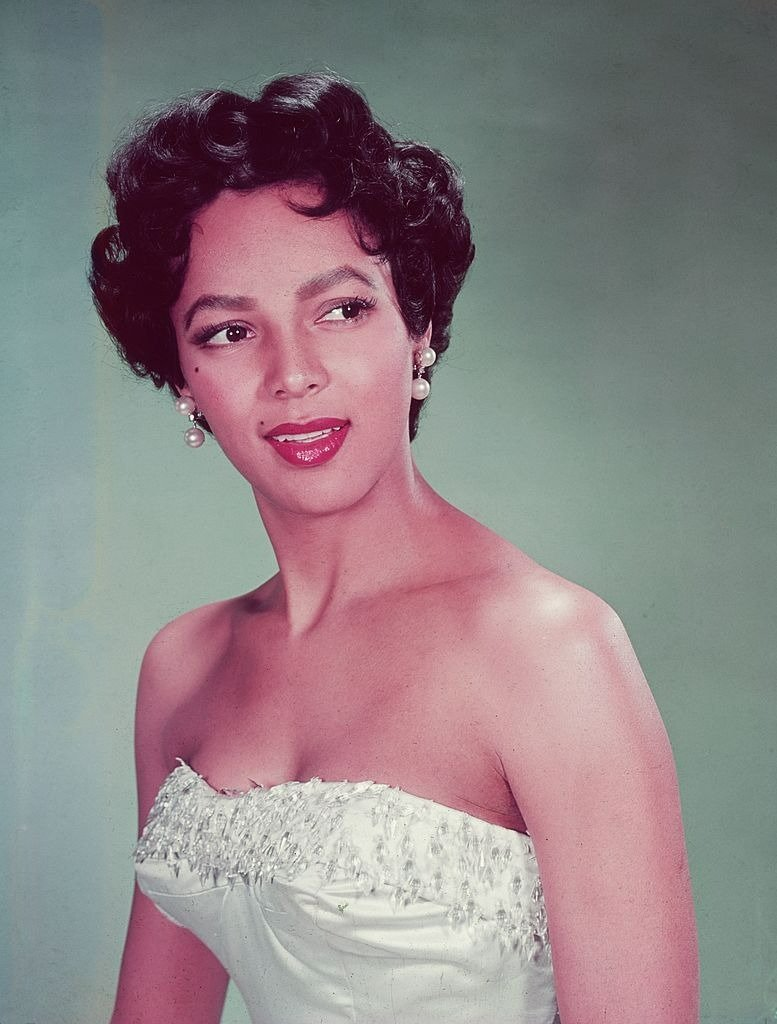 Headshot portrait of American actor Dorothy Dandridge wearing a white strapless dress with a beaded bodice, looking to the side   Photo: Getty Images