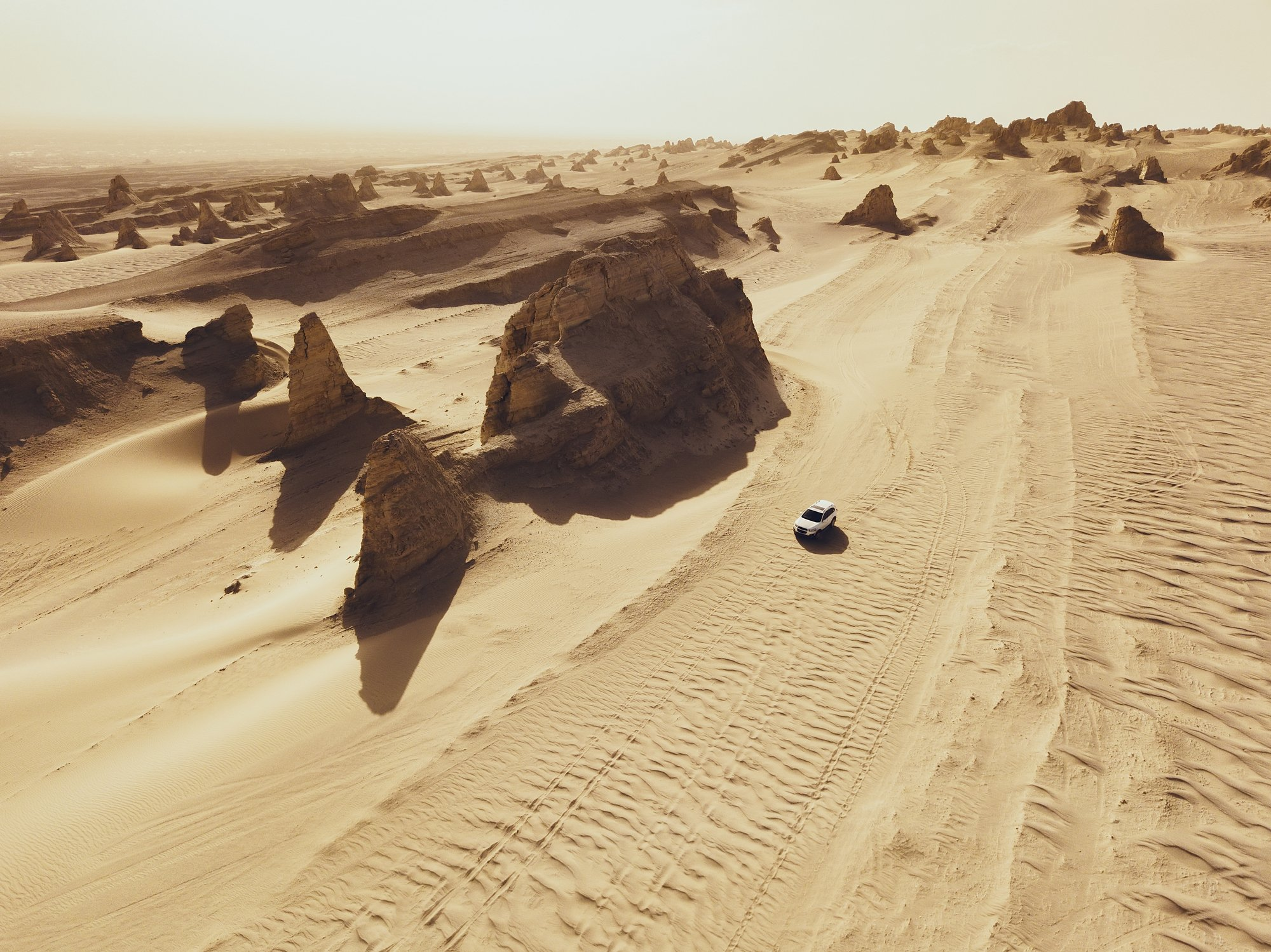 Aerial view of white car on desert road    Photo: Getty Images