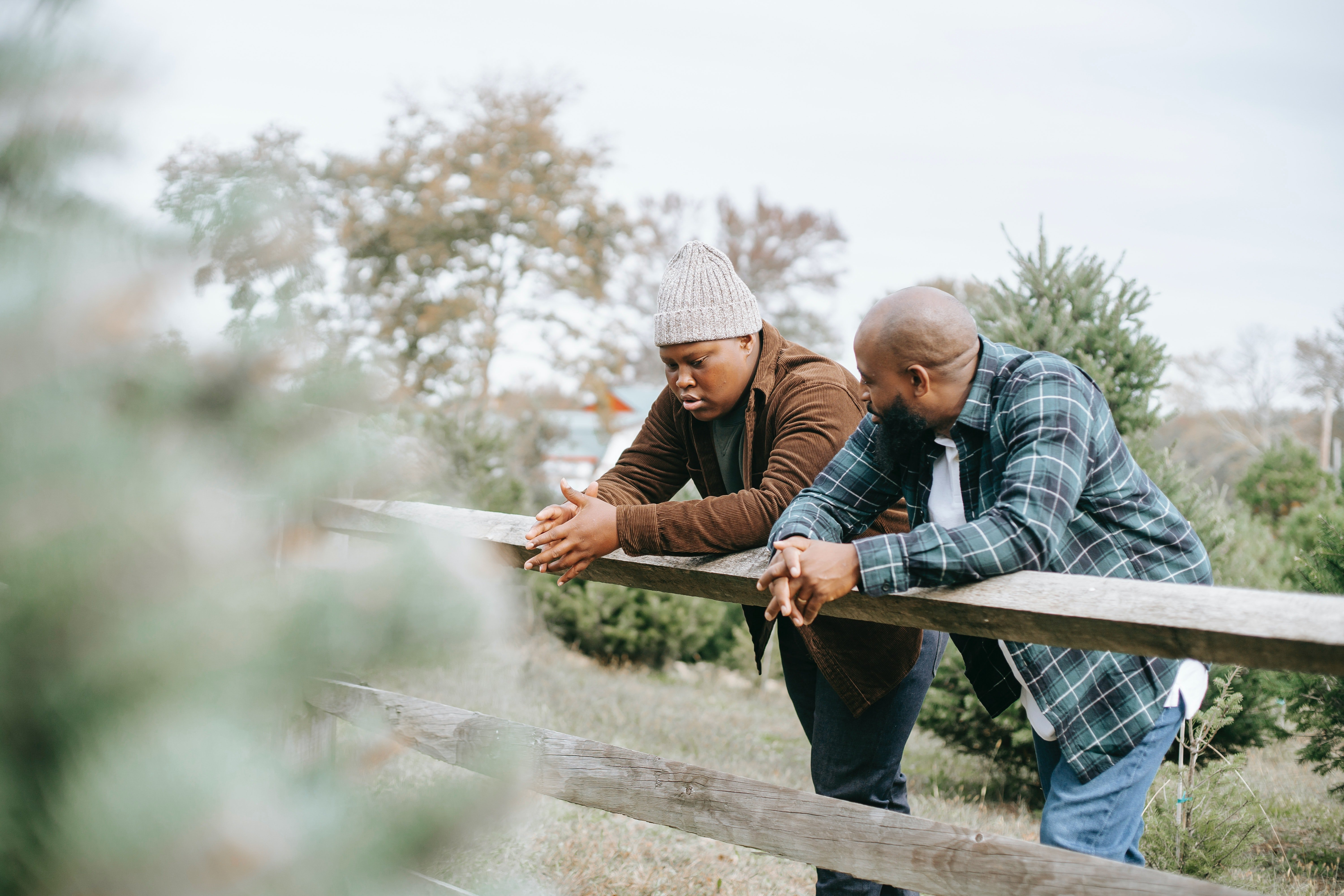 Black father conversing with teen near fence on farmland   Photo: Pexels