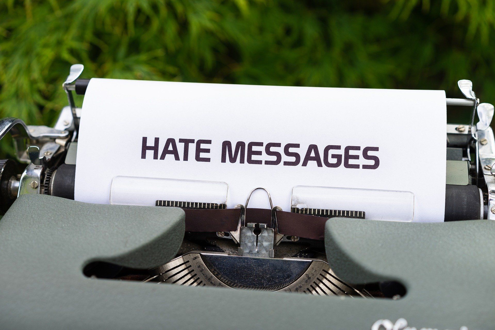 """Pictured: A typewriter showing a document that reads: """"Hate messages"""" referencing online cyberbullying 