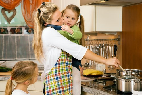 A young mother cooking while holding her daughter and talking over the phone. | Source: Shutterstock.