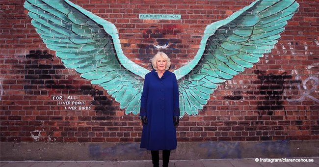 Camilla looks radiant posing in a bright blue coat and knee-high boots near Liver Bird wings