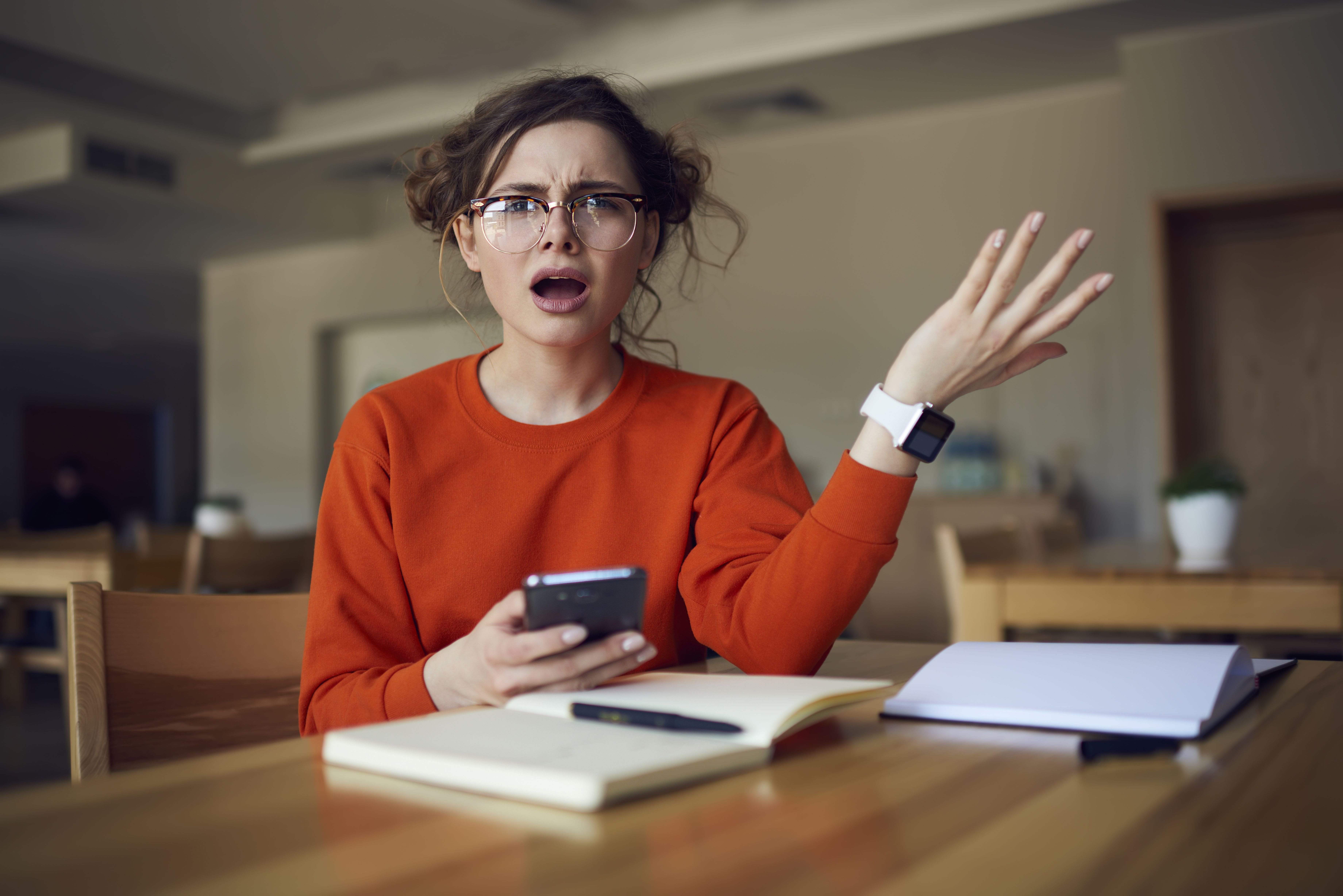 A woman looks shocked while going through her phone.   Source: Shutterstock