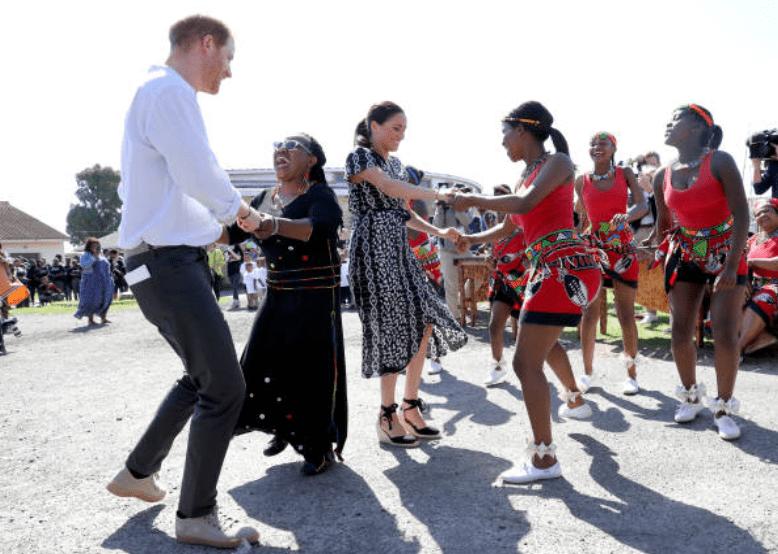 Lors de leur tournée en Afrique, Prince Harry et Meghan Markle dansent avec les habitants lors d'une visite organisée à l'initiative de la justice dans la banlieue de Nyanga, le 23 septembre 2019 à Cape Town, en Afrique du Sud.|Source: Getty Images