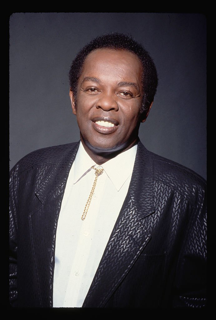 A portrait of Lou Rawls posing in a black blazer and a bolo tie around his collar. | Photo: Getty Images