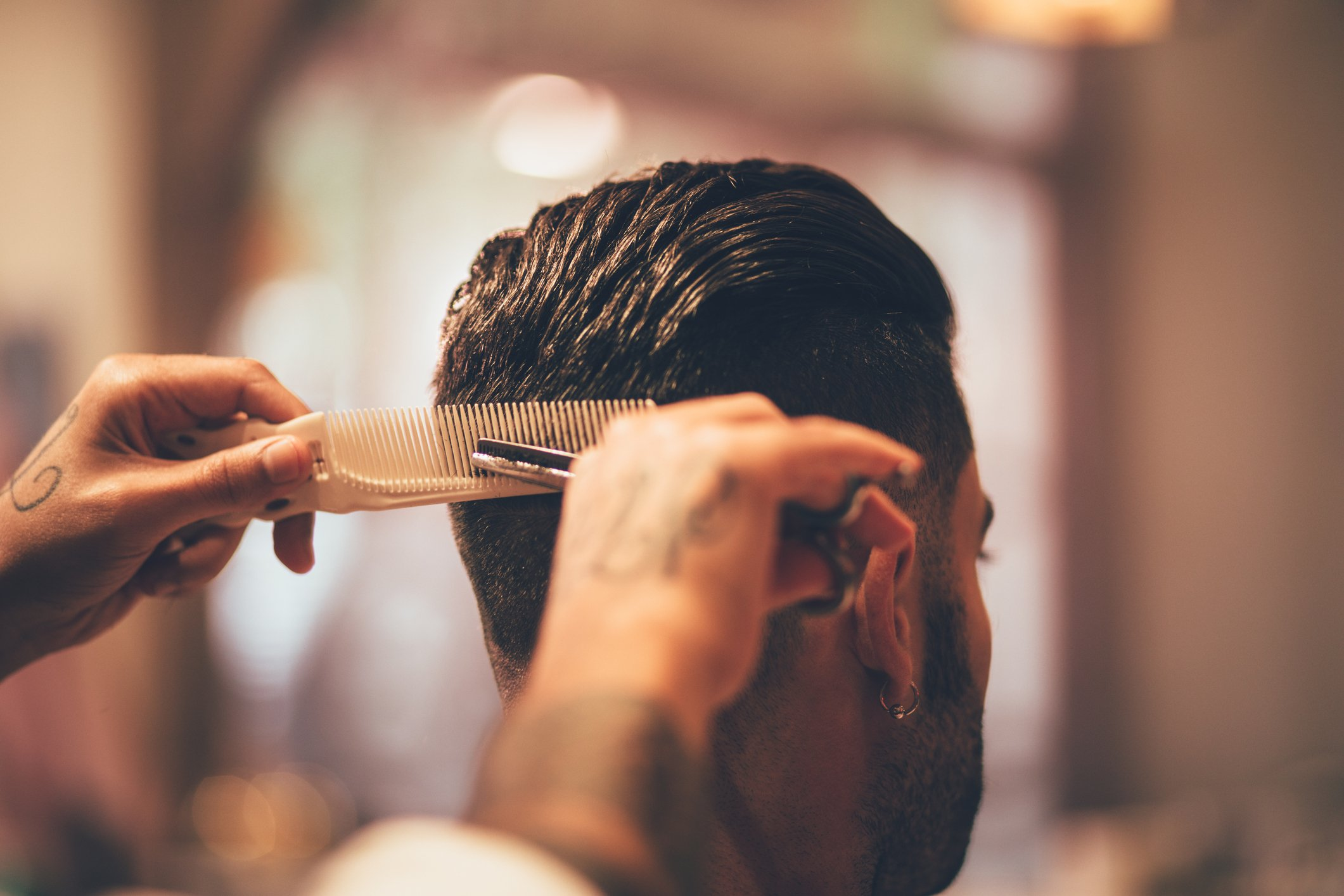 A close-up photo of a hairstylist cutting a man's hair.   Photo: Getty Images