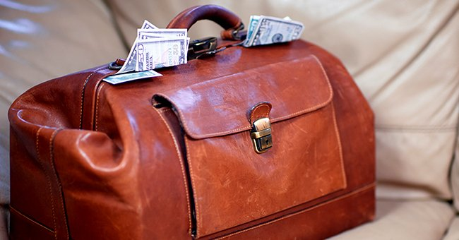 Money coming out of a red leather bag.   Source: Shutterstock