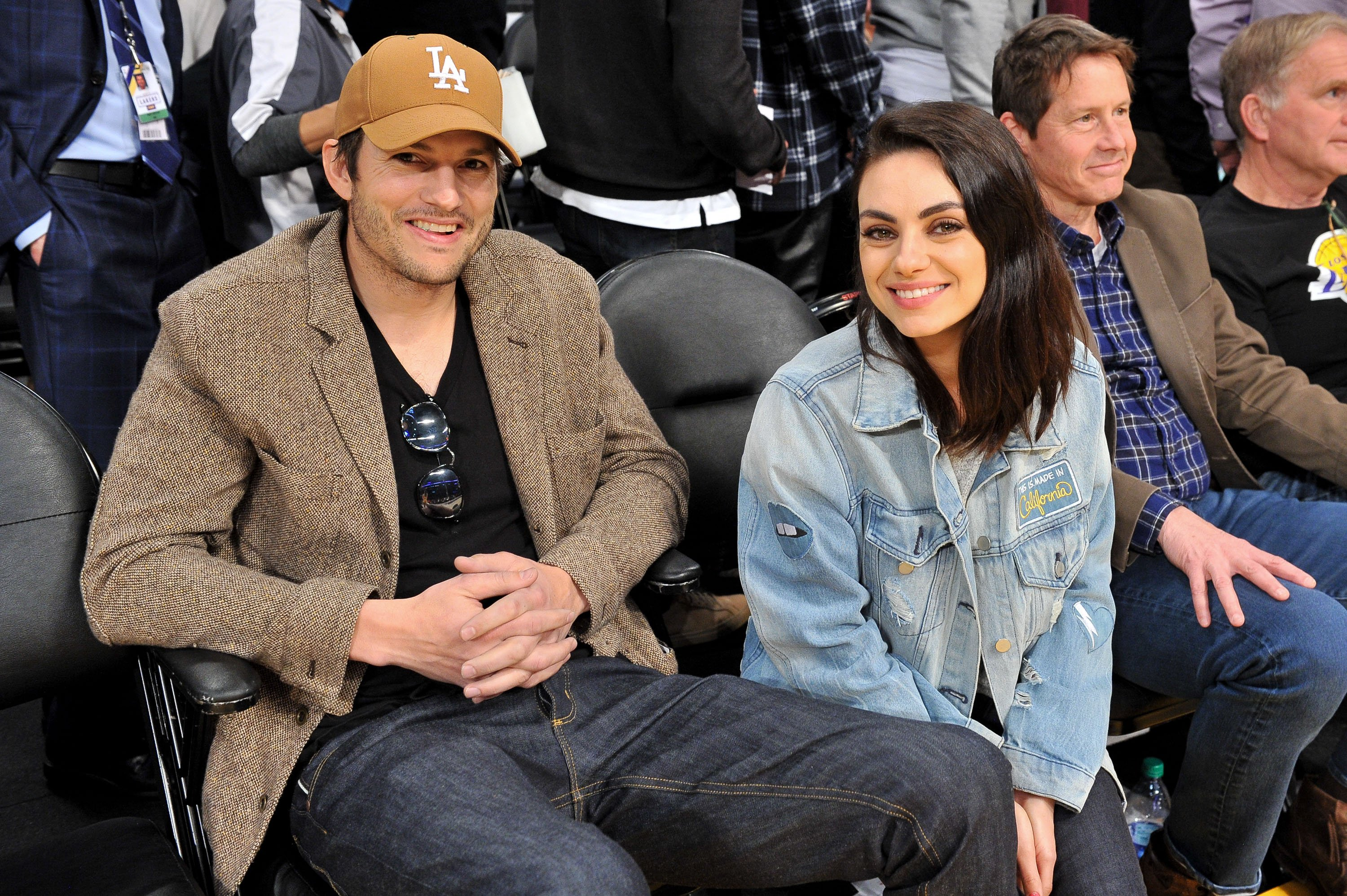Ashton Kutcher and Mila Kunis smile for the camera at an L.A. Lakers game, January, 2019. | Photo: Getty Images.