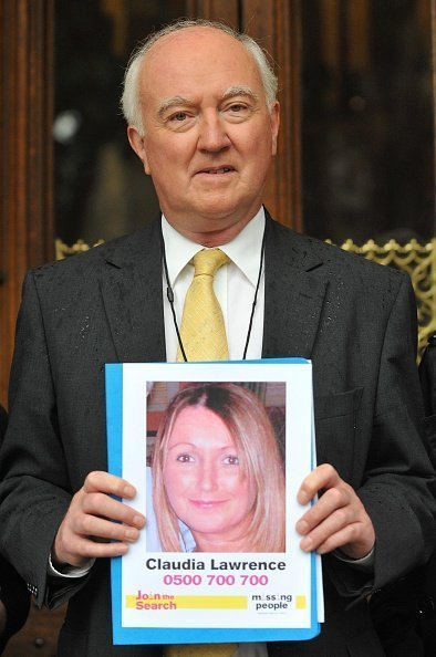 Peter Lawrence, father of missing Claudia Lawrence, holds up poster of his missing loved one | Photo: Getty Images