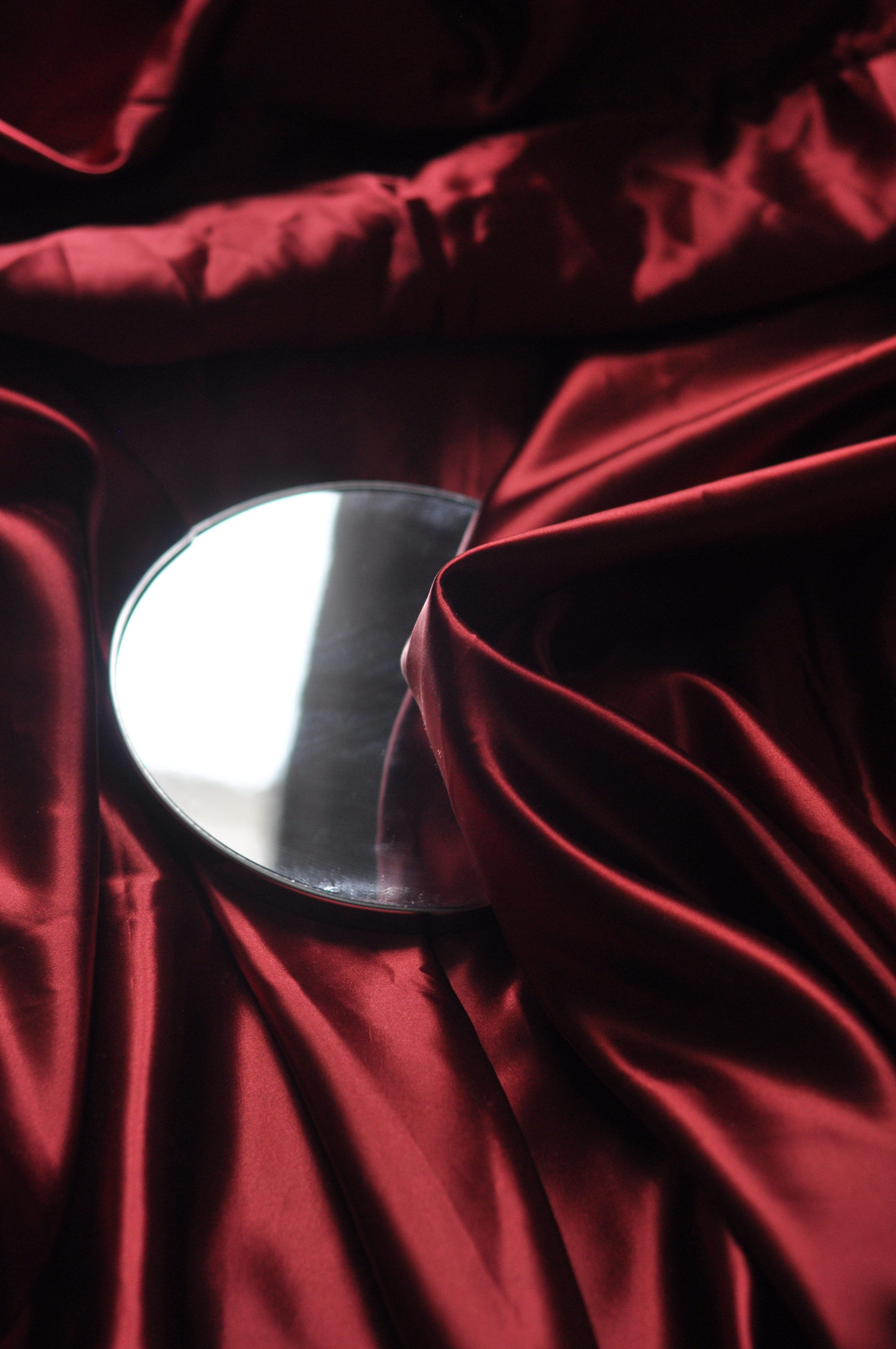 A mirror on top of some red silk | Photo: Unsplash