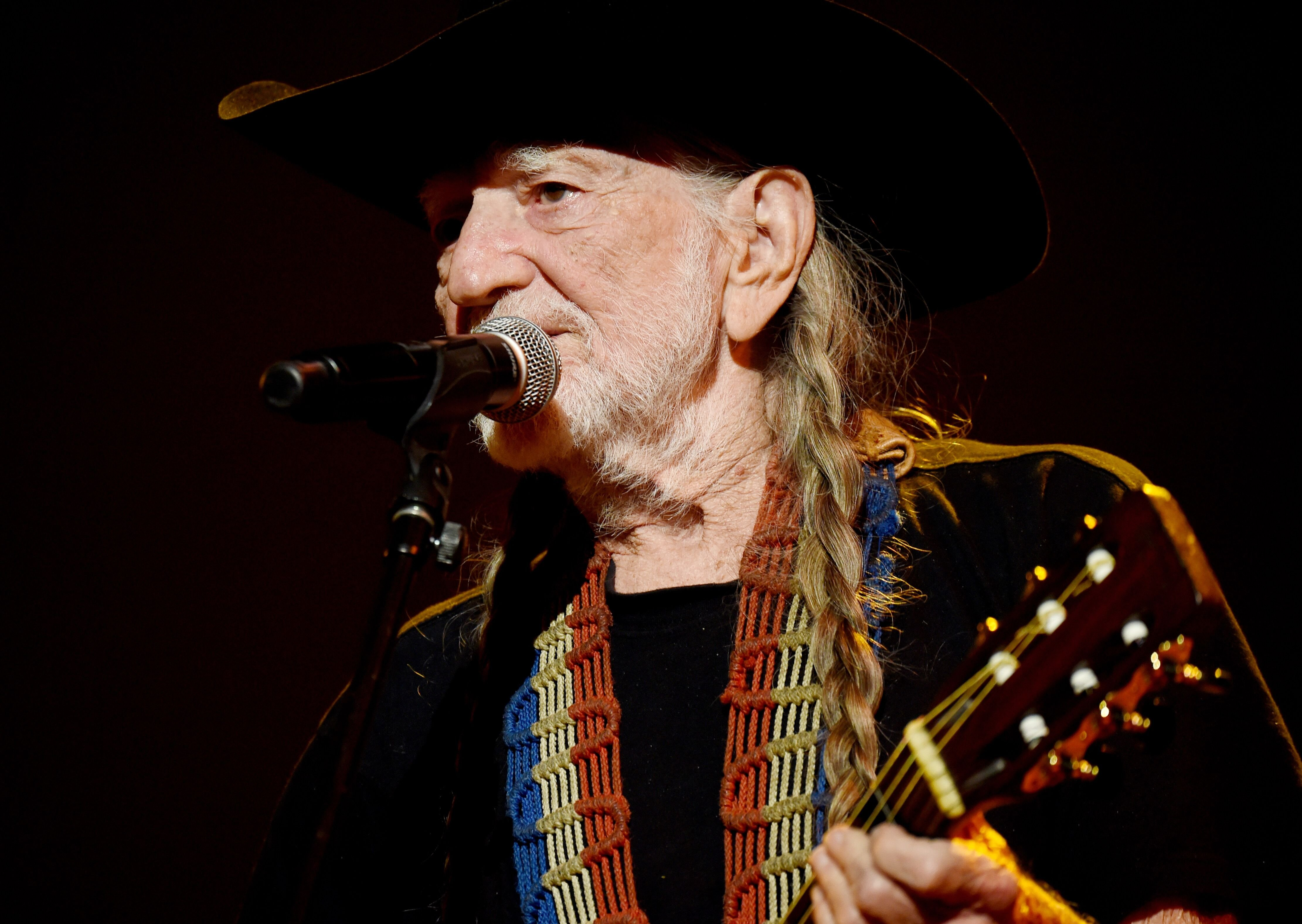 Willie Nelson performs onstage at the 25th anniversary MusiCares 2015 Person Of The Year Gala. | Source: Getty Images