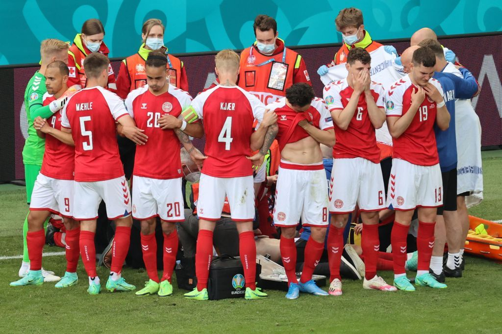 Denmark's players forming a barrierr as paramedics attend to midfielder Christian Eriksen during the UEFA EURO 2020 Group B football match between Denmark and Finland at the Parken Stadium in Copenhagen, Denmark | Photo: Wolfgang Rattay/AFP via Getty Images