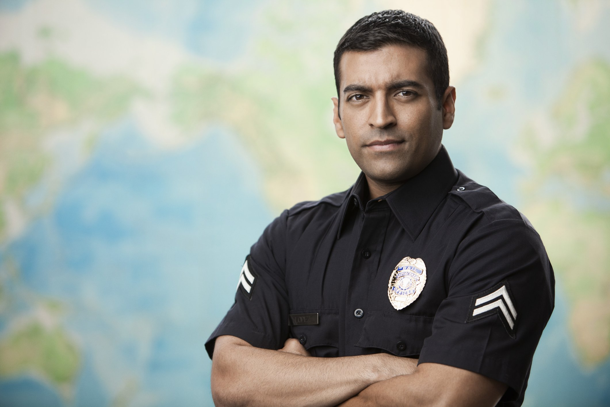 Serious Hispanic policeman with arms crossed.   Photo: Getty Images