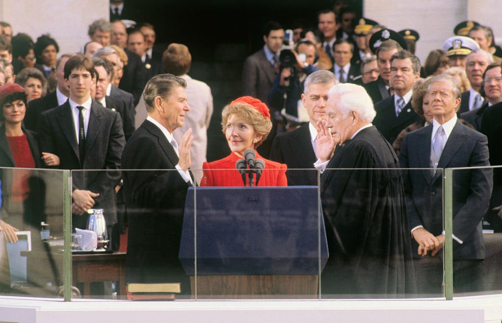 President-elect Ronald Reagan takes the oath of office during inauguration ceremonies in Washington, DC. His wife, Nancy, is holding the Bible and Chief Justice Warren Burger is administering the oath. | Source: Getty Images