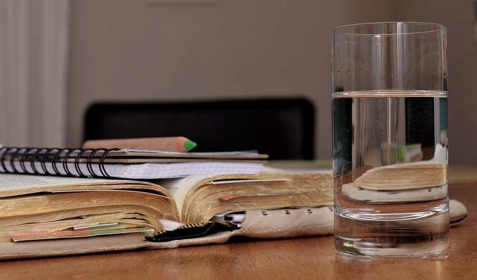 A glass of water on a table beside a book| Photo: Pixabay