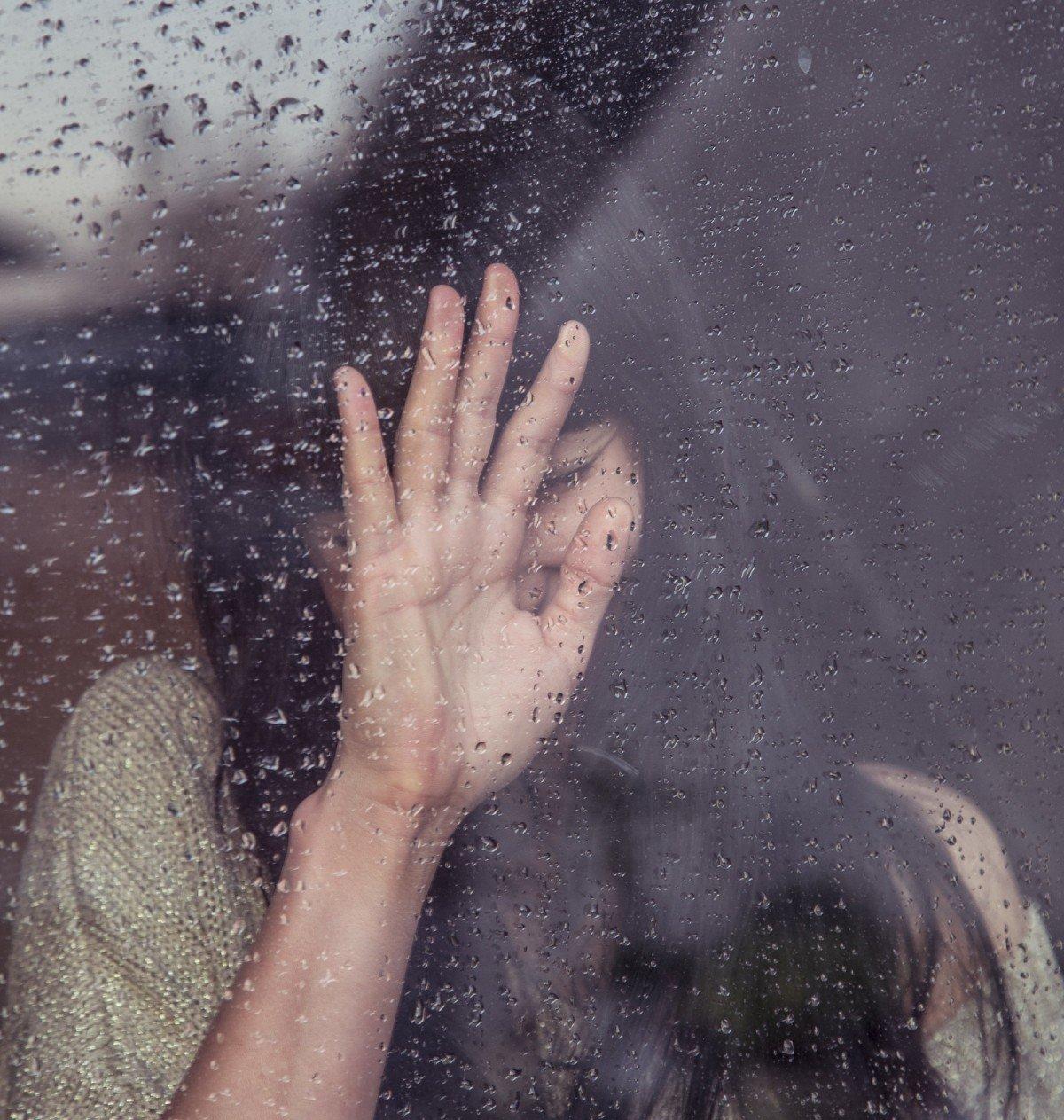 Mujer llorando contra ventana en día lluvioso. | Imagen: PxHere