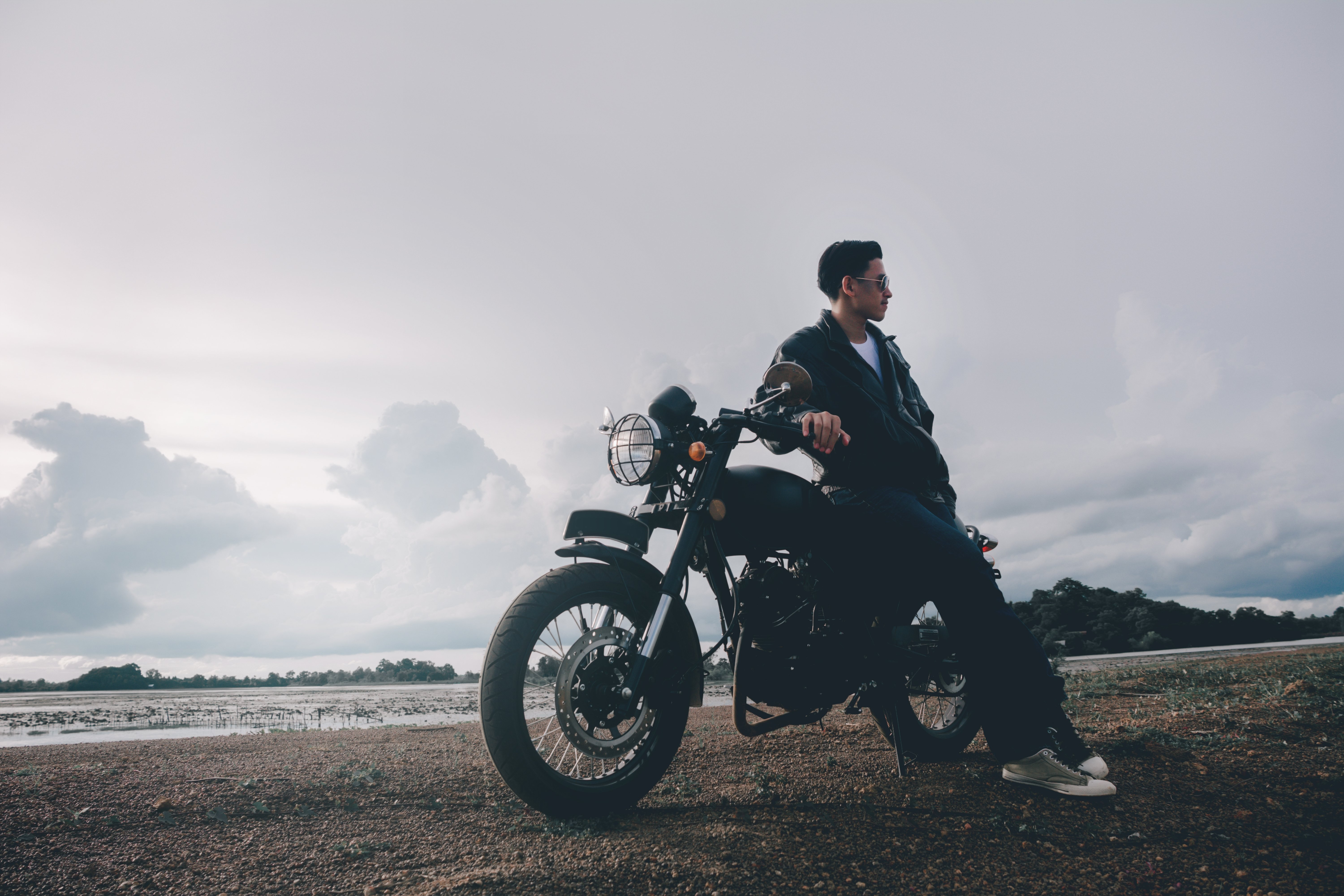 Young man posing with his motorcycle underneath the sunset. |Source: Shutterstock