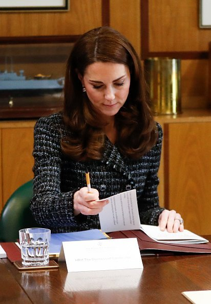 "The Duchess of Cambridge attends to some paperwork at a ""Mental Health In Education"" conference on February 13, 2019 