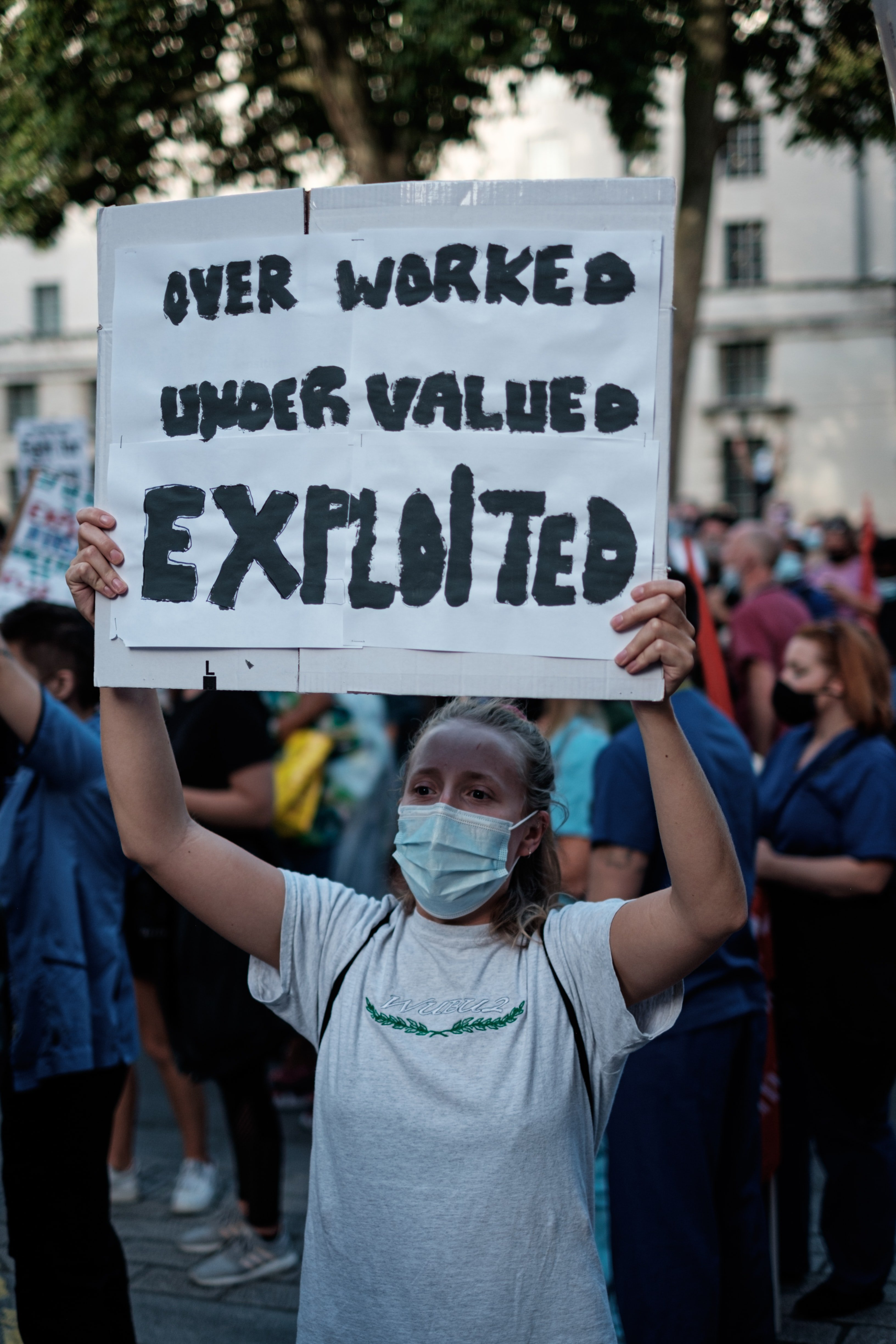 """A protestor stands in the street holding up a poster that states """"Over Worked, Under Valued, Exploited"""" 