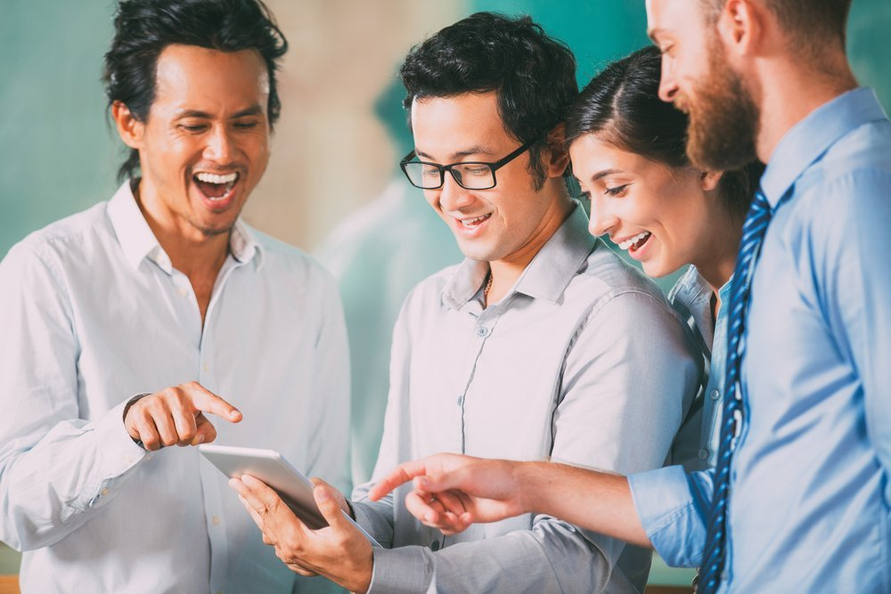 Cheerful team laughing and pointing at tablet | Photo: Shutterstock.com